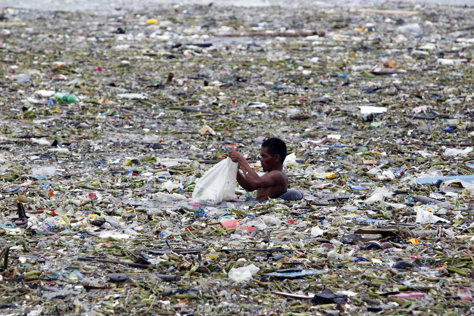 A man collects plastic and other recyclable materials from debris in the waters of Manila Bay after tropical storm Saola hit the Philippine capital